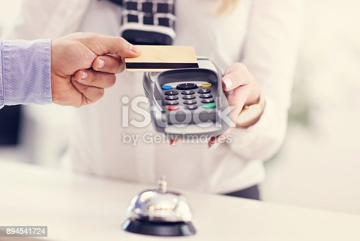 istock People paying in hotel reception 894541724