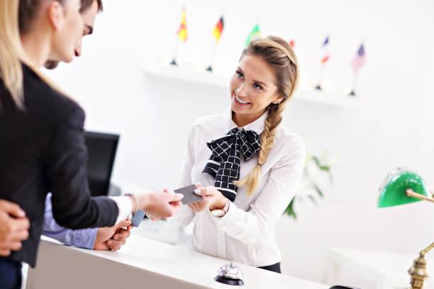 ホテルのフロントで金を払う人 - 受付係 ストックフォトと画像