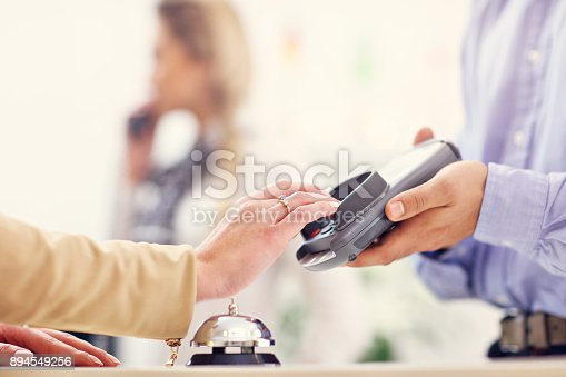 istock People paying in hotel reception 894549256