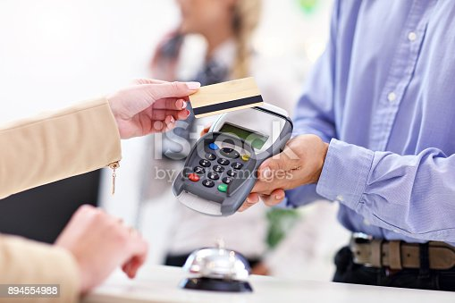 istock People paying in hotel reception 894554988