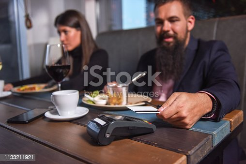 istock People paying in restaurant by credit card reader 1133211921