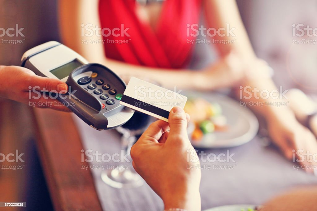 People paying in restaurant by credit card reader stock photo