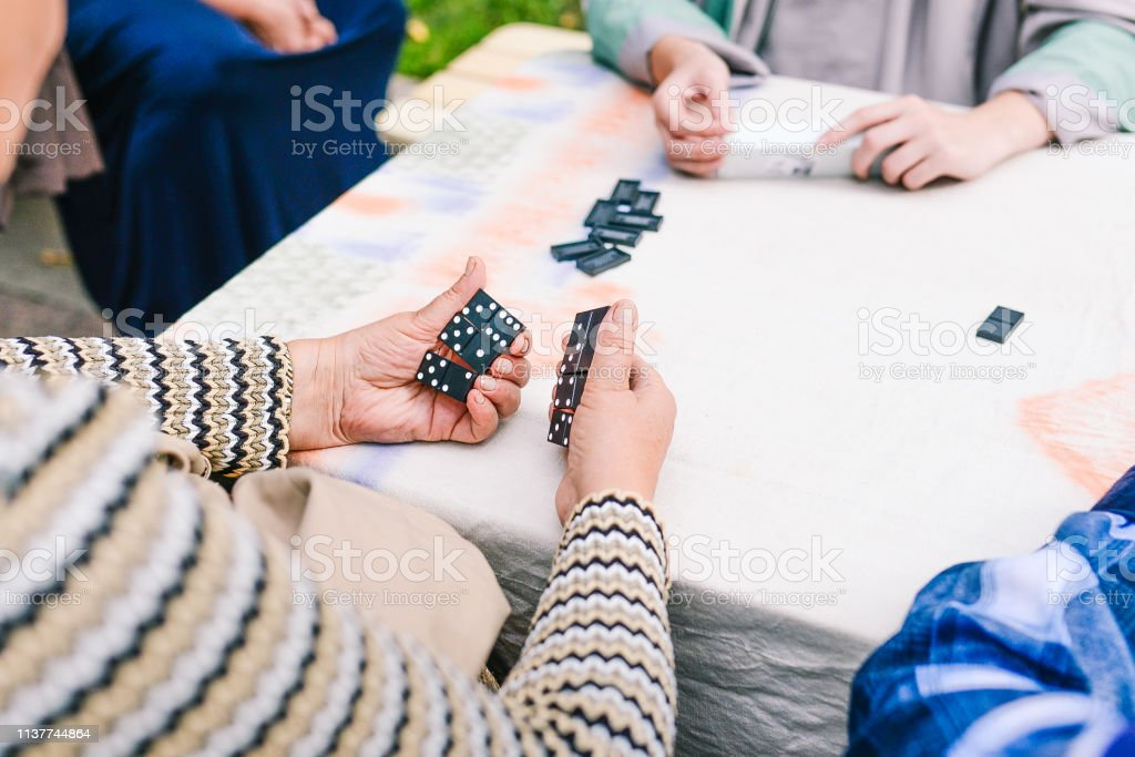 People play dominoes. Several people have fun playing dominoes on the...