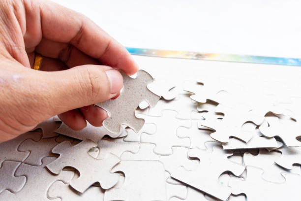 people play jigsaw and try to find a missing one - foto stock