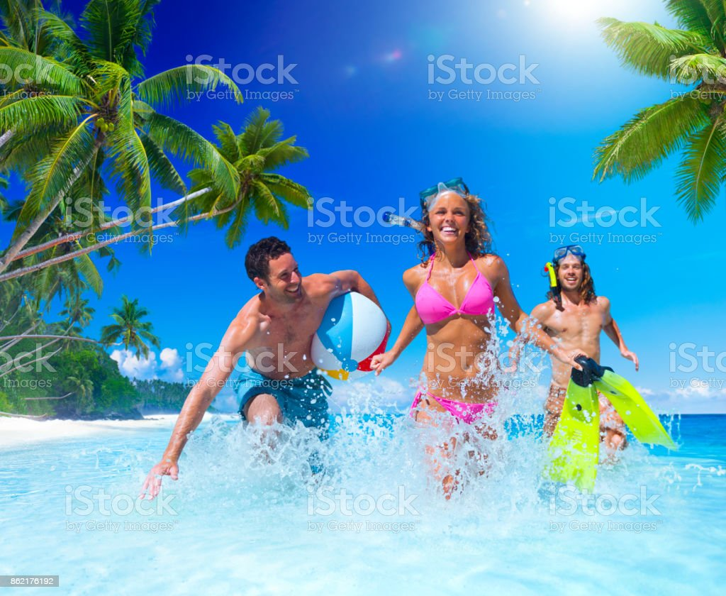 People playing at a tropical beach. stock photo
