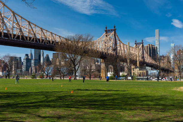 People playing baseball at Queensbridge Park in a sunny day. Ed Koch Queensboro Bridge in the background - foto stock
