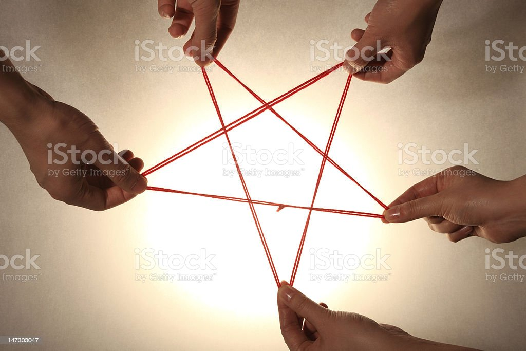 People playing cats cradle game,close-up stock photo