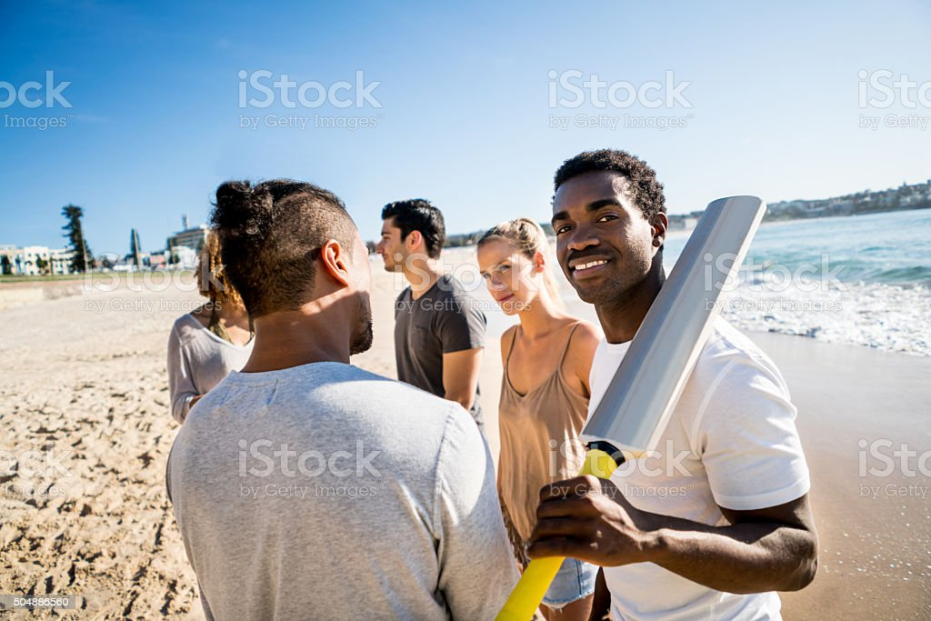 People playing cricket at the beach stock photo