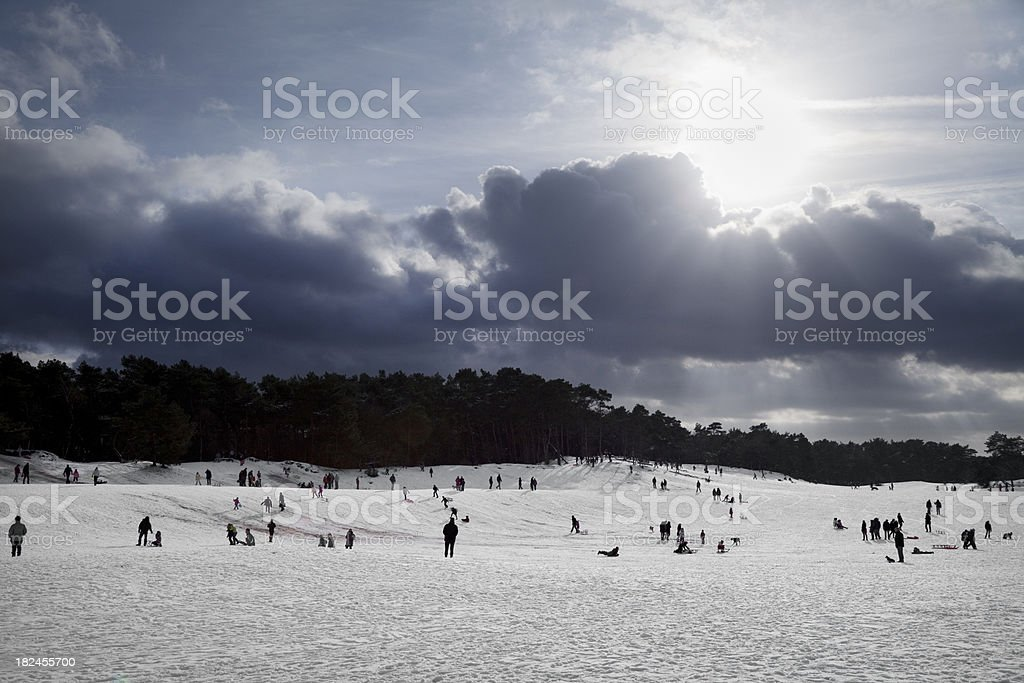 People playing in snow on a sunny winter day (XXXL) royalty-free stock photo