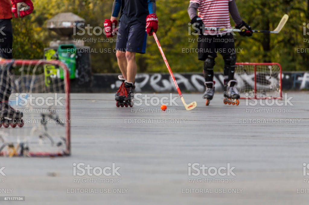 People playing street hockey with sticks and rollers stock photo