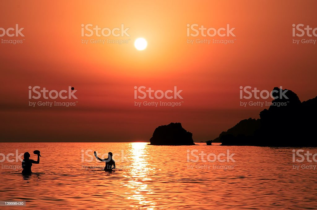 People playing tennis at sunset royalty-free stock photo
