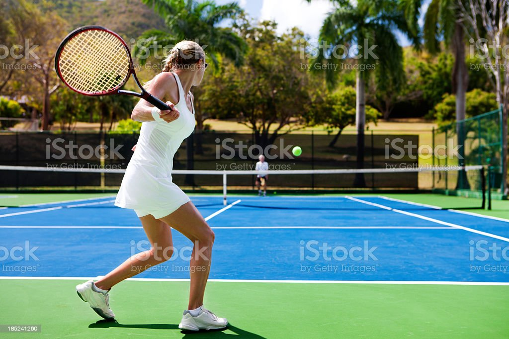 people playing tennis in tropics stock photo