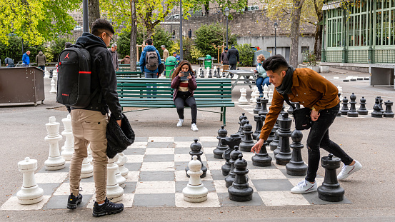 People playing traditional oversized street chess in Parc des Bastions.