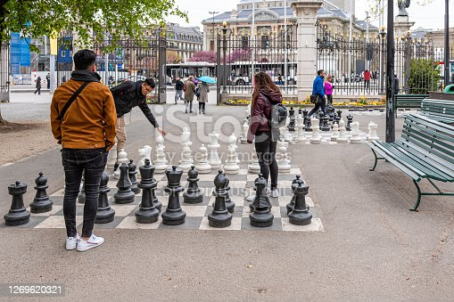 Geneva, Switzerland - April 16, 2019: People playing traditional oversized street chess in Parc des Bastions - image