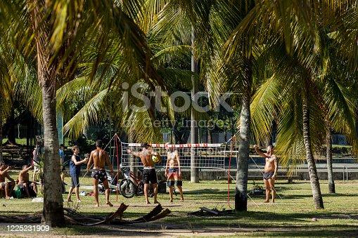 Rio de Janeiro, Brazil - May 10, 2020: Urban street scene during the COVID-19 Corona virus outbreak with people enjoying sports among palm trees