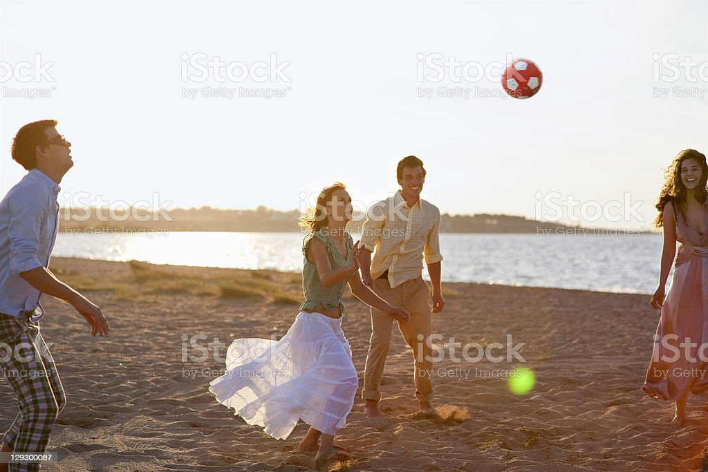 People playing with soccer ball on beach stock photo