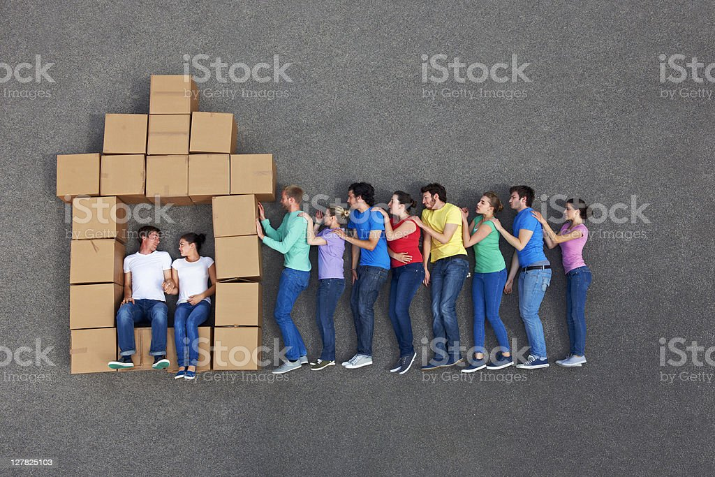 People posing by cardboard box house stock photo
