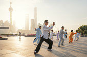 Shanghai, China - October 28, 2015: People practice tai chi in the Bund area as the Oriental Pearl Tower and other commercial buildings stand in the Lujiazui district.