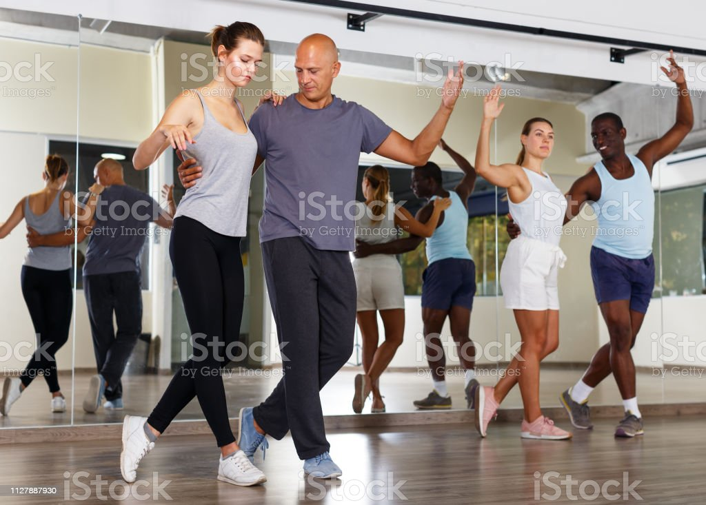Young positive people practicing vigorous jive movements in dance...