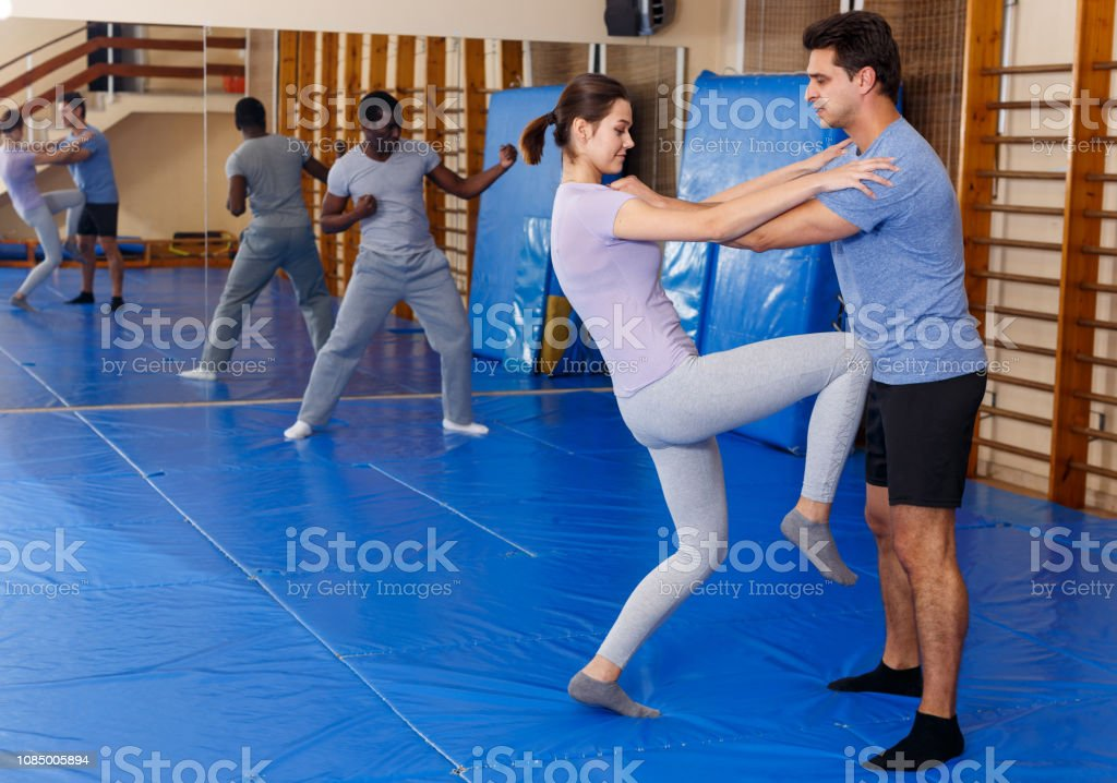 Young man and woman at self protection workout, training attack...