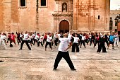 Elche, Alicante- October 20, 2019: People practicing Tai Chi for the fight against breast cancer in the square of the church of Santa Maria in a cloudy day