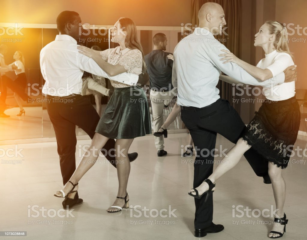 Couples of young people practicing vigorous jive movements together...