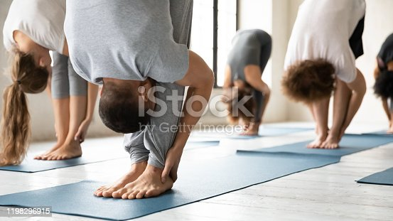 Young sporty people wearing sportswear practicing yoga at group lesson, standing in uttanasana pose on mats close up, doing forward bend, head to knees exercise, stretching in modern yoga studio