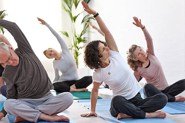People practicing yoga at health club Group of mature people practicing yoga at health club yoga class stock pictures, royalty-free photos & images