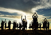Silhouettes of people doing yoga on the beach at sunset
