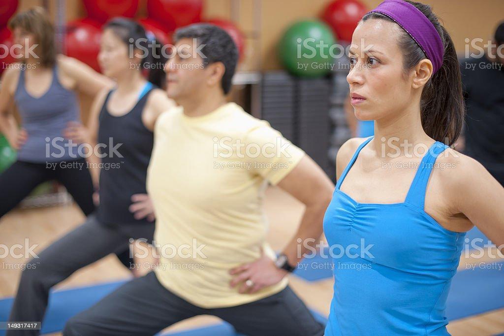 People practicing yoga in studio stock photo