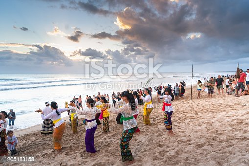 BALI, INDONESIA - August 1, 2017: People praying during celebration Balinese ceremony at Pura Goa Lawah temple, Bali, Indonesia.