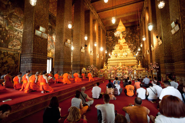 people praying with monks of historical monastery wat pho - religious celebration stock photos and pictures