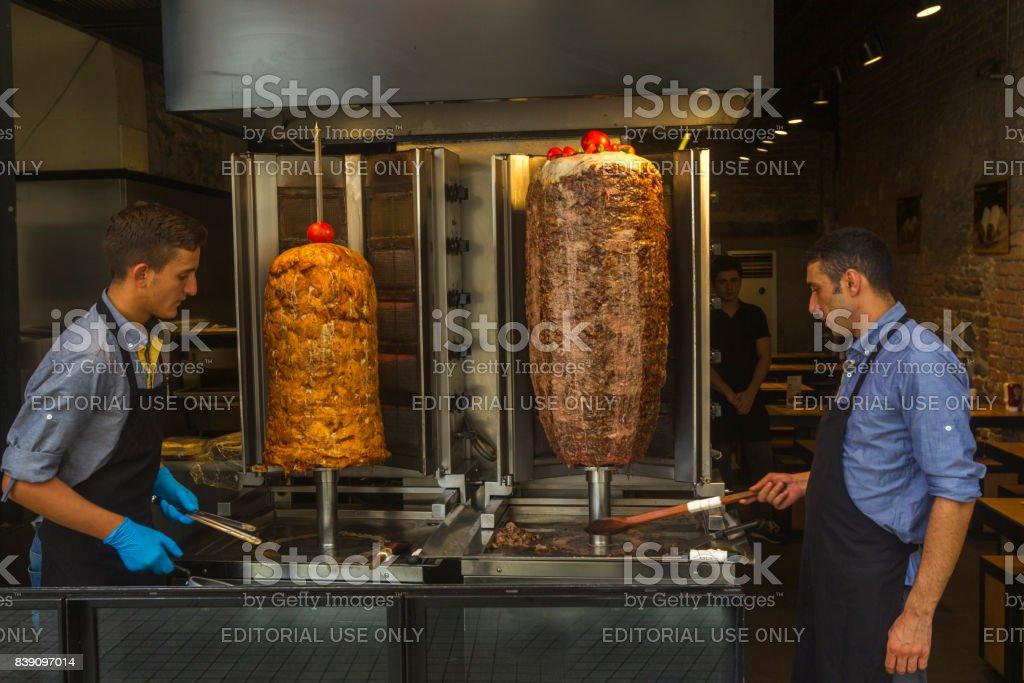people preparing doner kebap at entrance of restaurant in istiklal street of beyoglu istanbul turkey stock photo