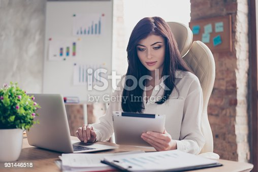 istock People profession occupation start-up investment idea concept. Pretty pensive busy concentrated confident with long dark hair economist reading email from partners colleagues in luxury office 931446518