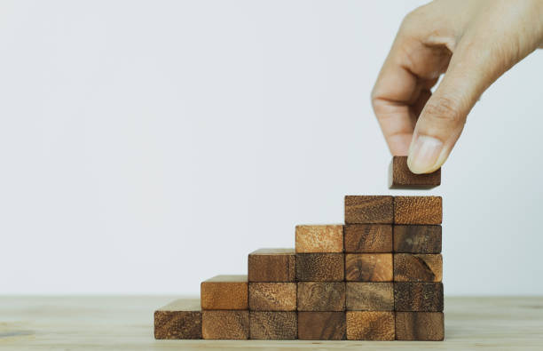 People put up stacking a wood block, Business building success, plan and strategy of business concept. risk of business.