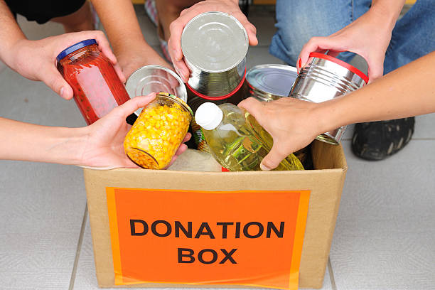 People putting food in a donation box stock photo