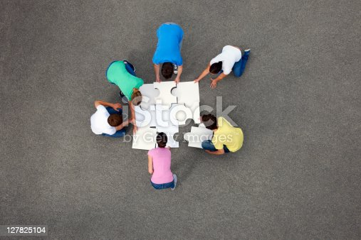 istock People putting together jigsaw puzzle 127825104