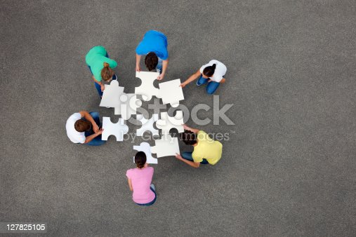 istock People putting together jigsaw puzzle 127825105