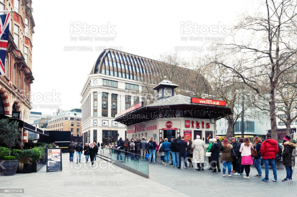 People queue for buying tickets from TKTS, the official London theatre ticket booth located at Leicester Square offering last minute and discount tickets for West End shows stock photo