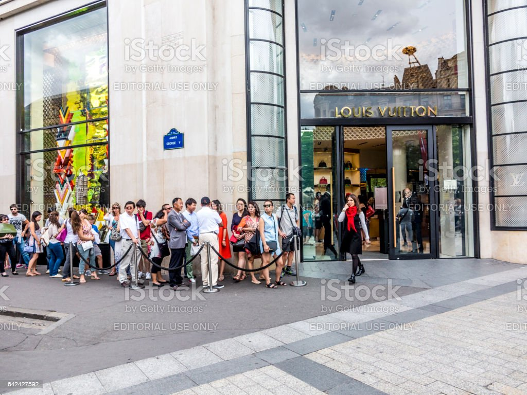 people queue up in front of Louis Vuitton shop stock photo