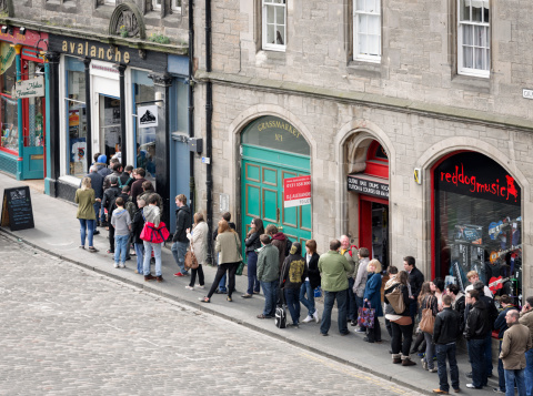 Edinburgh, UK - April 16, 2011: A long queue of people on the pavement outside Avalanche Records on Record Store Day.  Held annually since 2008, Record Store Day is celebrated around the world in independant record shops.  Avalanche Records has been trading for more than 20 years, and is one of Scotlands largest independant music shops.