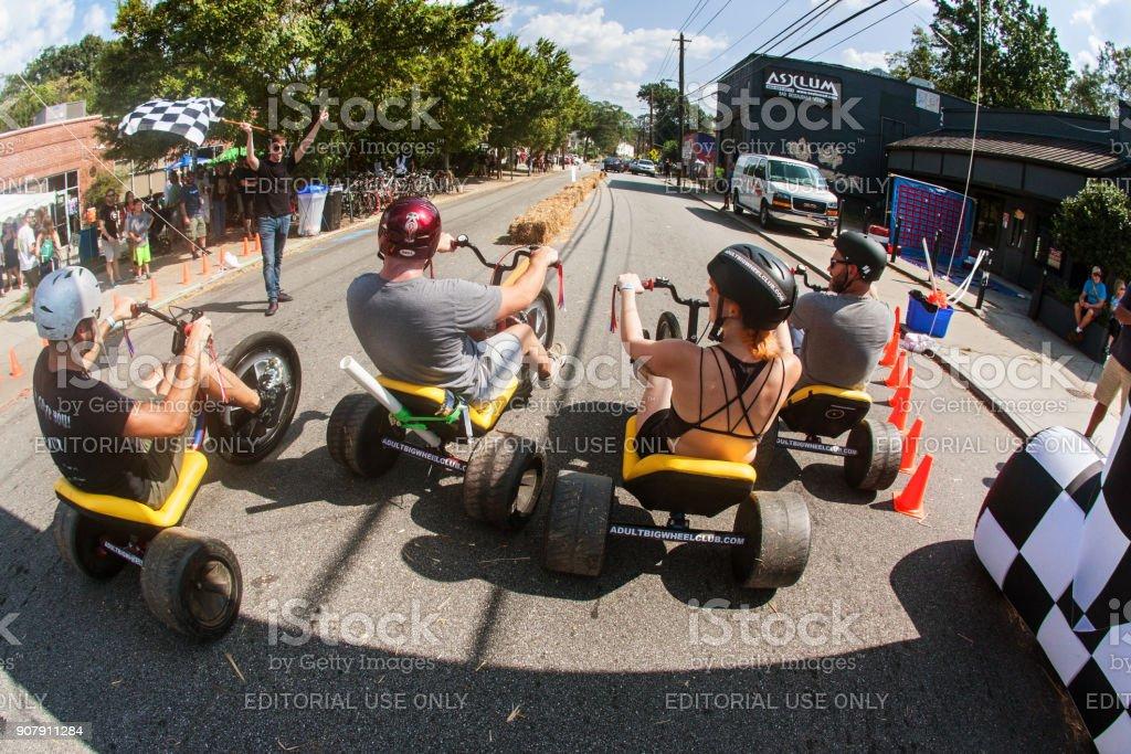 People Race Adult Big Wheels In Atlanta Fall Festival stock photo