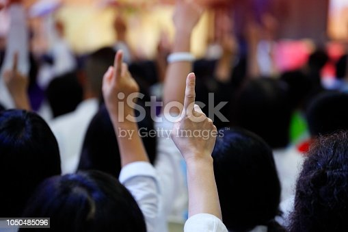 istock people reacting to the question by raising their index finger together as teamwork for unity and unanimous agreement and collabora 1050485096