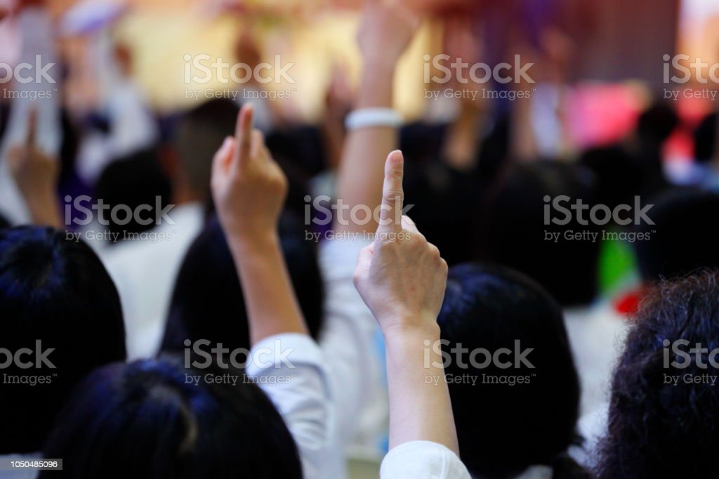 people reacting to the question by raising their index finger together as teamwork for unity and unanimous agreement and collabora stock photo