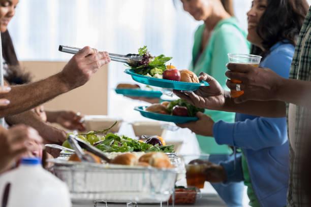 mensen ontvangen voedsel van vrijwilligers in gaarkeuken - portie stockfoto's en -beelden