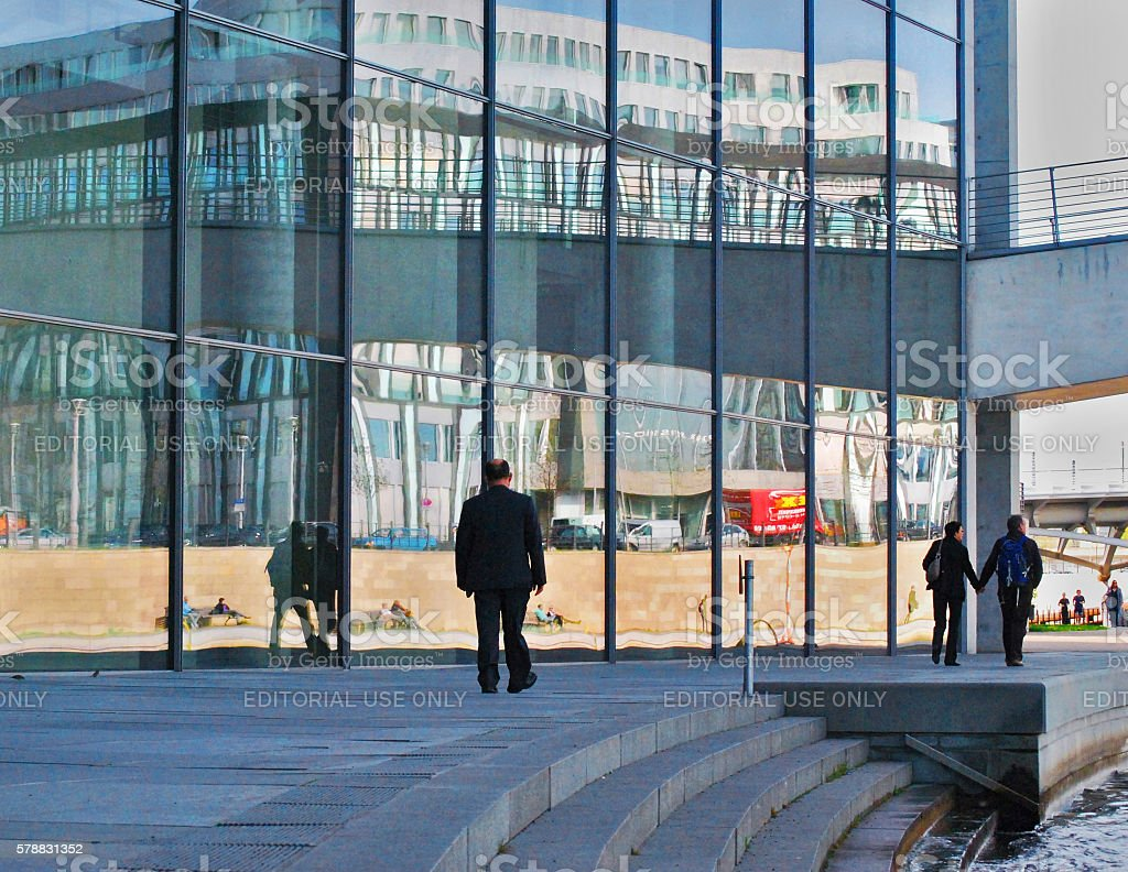 People reflected in the windows of a government building, Berlin stock photo