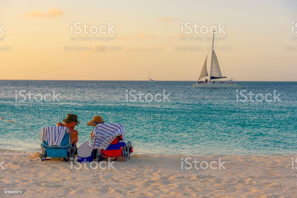 People relax and have fun during a caribbean sunset in Aruba. stock photo