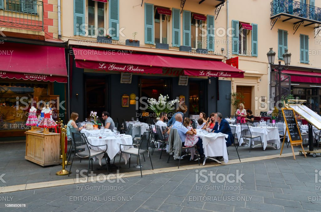 People relax at tables in outdoor French restaurant Le Grand Balcon in Old Town, Nice, Cote d'Azur, France stock photo