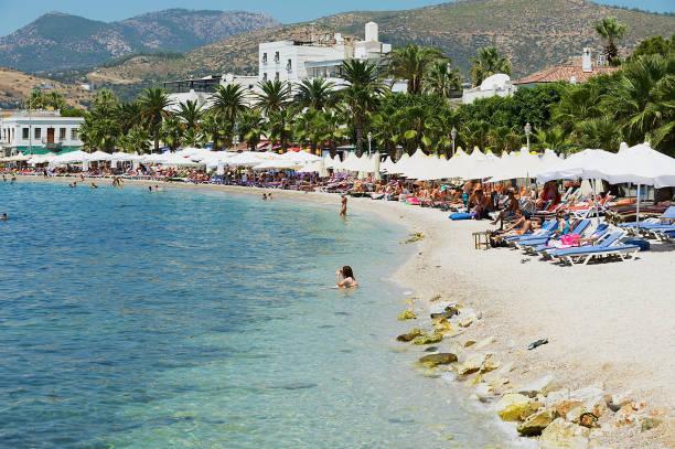 menschen entspannen sie am strand an der resort bodrum, türkei. - hotels in der türkei stock-fotos und bilder