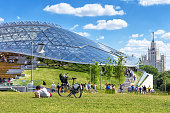 Moscow - June 17, 2018: People relax by the amphitheater with glass dome in Zaryadye Park in Moscow, Russia. Scenic Moscow centre on sunny summer day. Zaryadye is one of the main landmarks of Moscow.